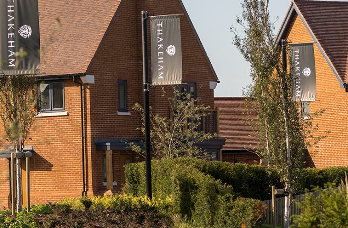 2 new Thakeham red brick buildings with poles showing a Thakeham banner amongst shrubbery within an estate