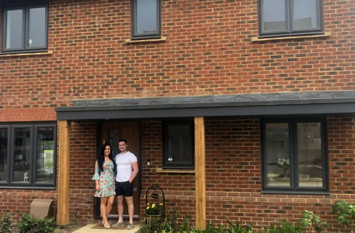 A young couple in summer clothing standing in front of their Thakeham new build home with black windows and a porch