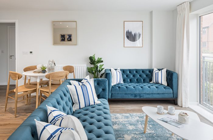An Alphium apartment living room. A white room with wooden flooring a wooden set of tables and chairs with 2 blue sofas facing patio doors
